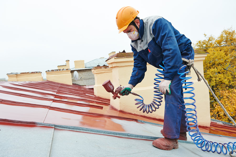 professional roofer working on roof painting